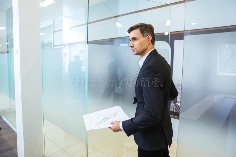 Confident businessman holding documents and entering the office. Confident businessman in formalwear holding documents and entering the office stock photo