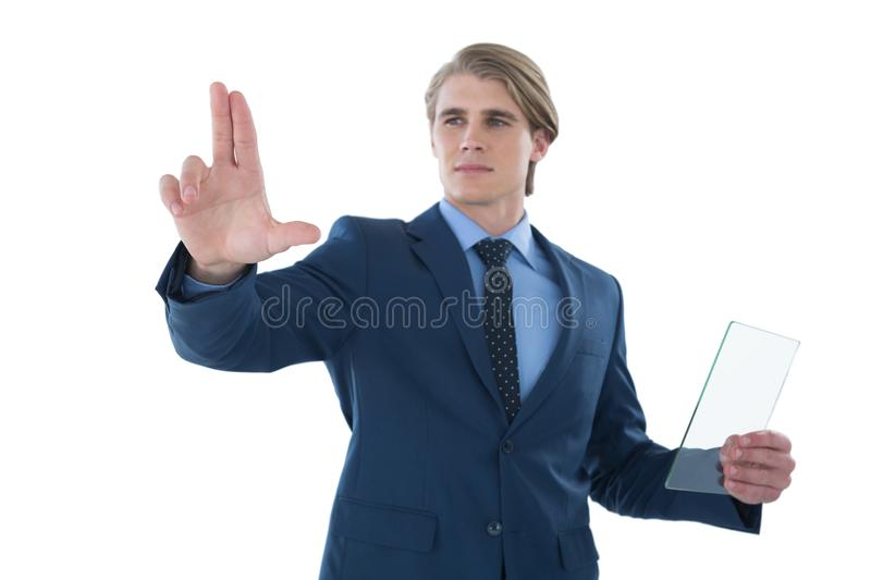 Confident businessman holding glass interface while touching imaginary screen. Against white background stock photos