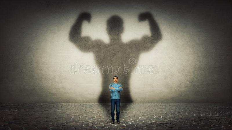 Powerful hero. Confident businessman imagine himself a powerful hero, casting shadow of big strong muscular bodybuilder showing his biceps. Inner strength royalty free stock images