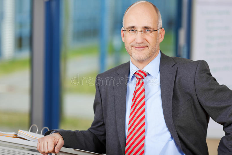 Confident Businessman Leaning On Podium royalty free stock photography
