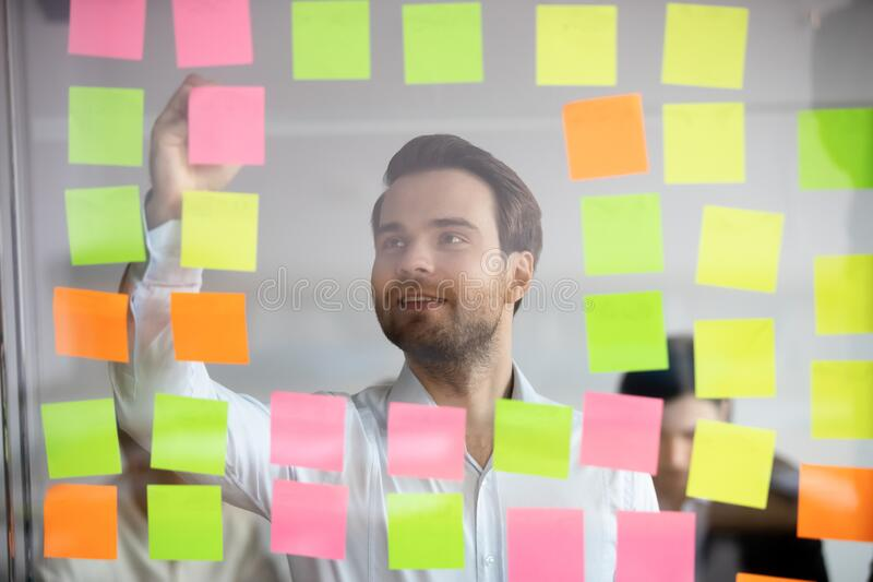Confident businessman mentor writing on sticky papers, post it notes royalty free stock images