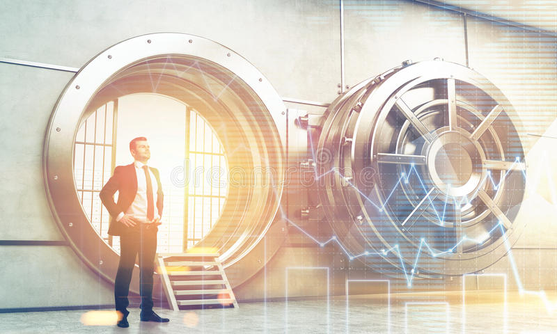 Confident businessman near open vault door with graphs stock photos