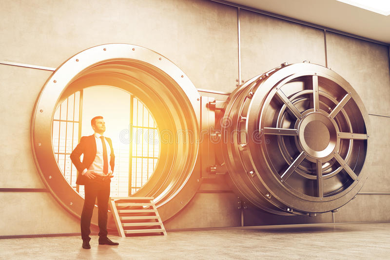 Confident businessman near open vault door, toned royalty free stock photography