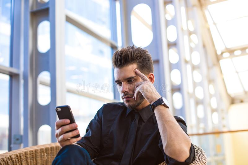 Confident businessman online booking via mobile phone, sitting in enterprise hall. stock photos