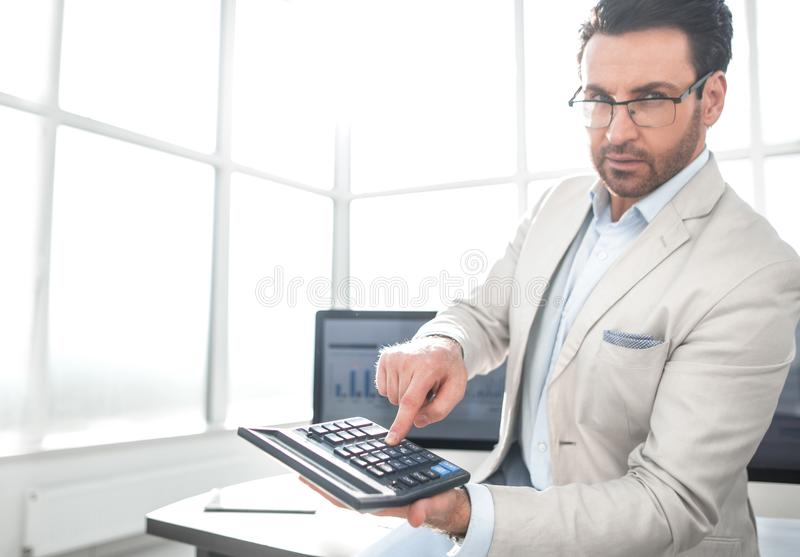 Confident businessman pointing to calculator stock photo
