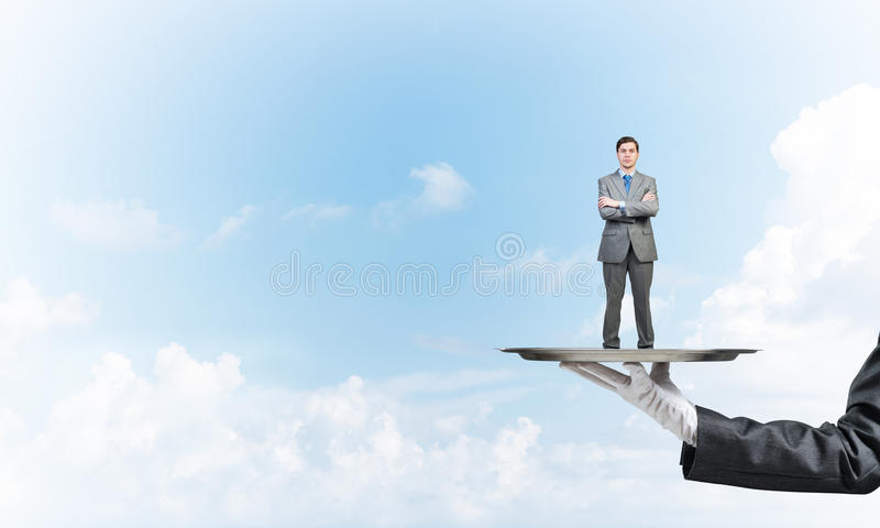 Confident businessman presented on metal tray against blue sky background stock image