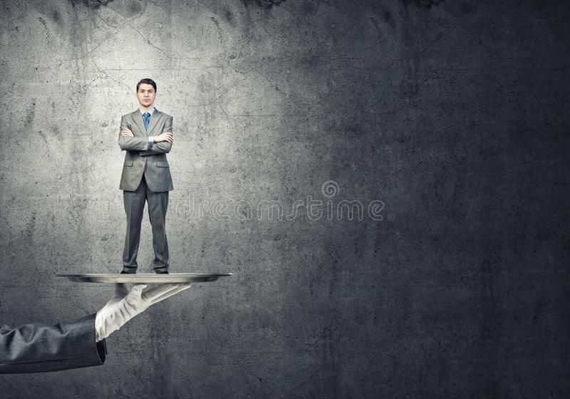 Confident businessman presented on metal tray against concrete wall background stock photo