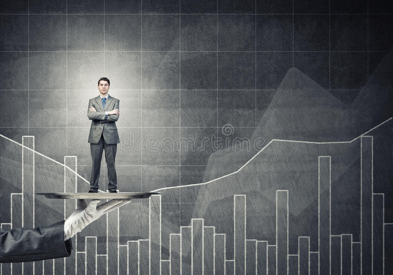 Confident businessman presented on metal tray against graphs and diagrams background stock images