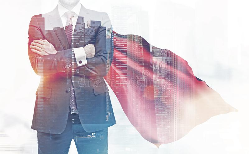 Confident businessman in a red cape, city royalty free stock photo