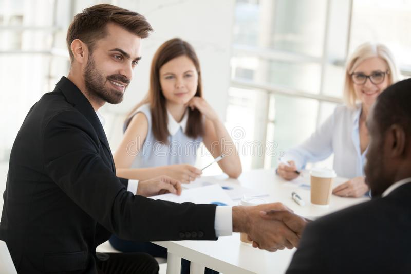 Confident businessman shaking hand colleague at company meeting stock photography