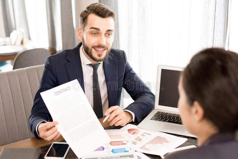 Confident businessman showing contract to colleague. Content confident handsome young businessman with beard showing contract to colleague and explaining terms royalty free stock image