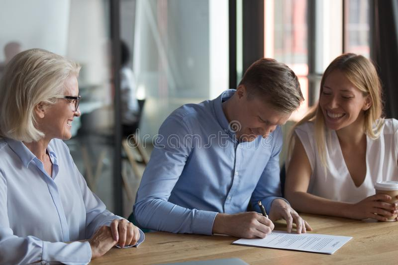 Confident businessman signing contract with partners, successful deal concept. Smiling men putting signature on paper document, purchasing real estate or stock photos