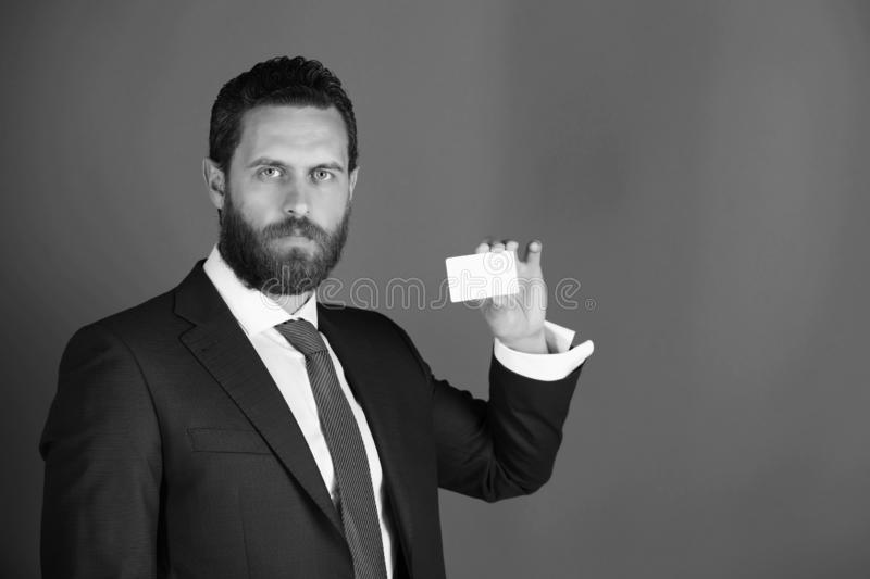 Confident businessman with silver business or credit card, business ethics. Confident businessman or bearded man with business or credit card in blue formal stock photos