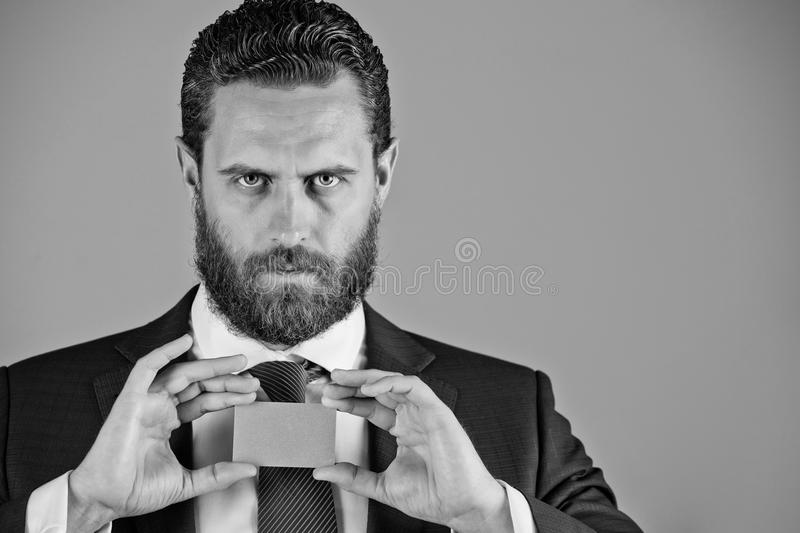 Confident businessman with silver business or credit card, business ethics. Confident businessman or bearded man with silver business or credit card in blue royalty free stock photography
