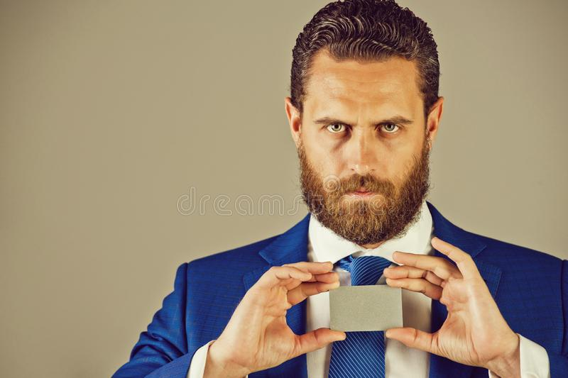Confident businessman with silver business or credit card, business ethics. Confident businessman or bearded man with silver business or credit card in blue royalty free stock image