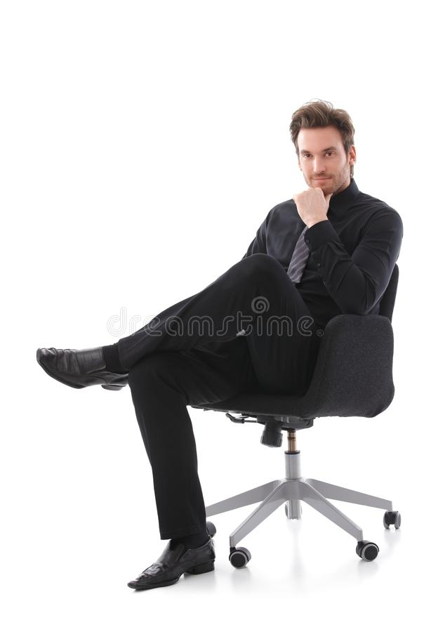 Confident businessman sitting on chair smiling. Confident handsome businessman sitting on chair, smiling royalty free stock image