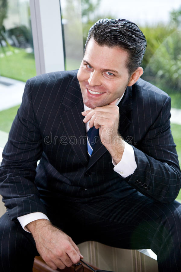 Download Confident Businessman Sitting In Office By Window Stock Photo - Image: 11529602