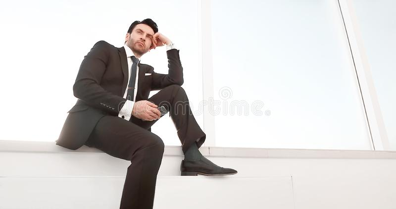 Confident businessman with a smartphone sitting in the office hallway royalty free stock image