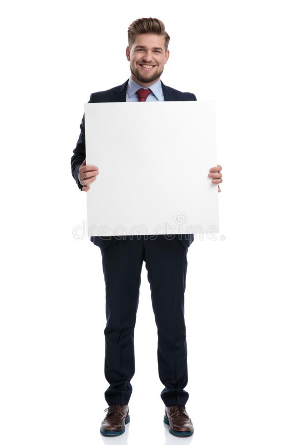 Confident businessman smiling and holding a blank billboard stock photos