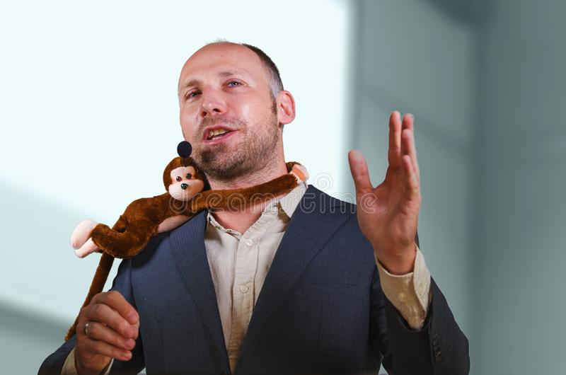 Confident businessman speaking at corporate business coaching and training auditorium conference room talking about monkey on. Young successful and confident stock image