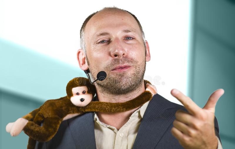 Confident businessman speaking at corporate business coaching and training auditorium conference room talking about monkey on. Young successful and confident royalty free stock photo