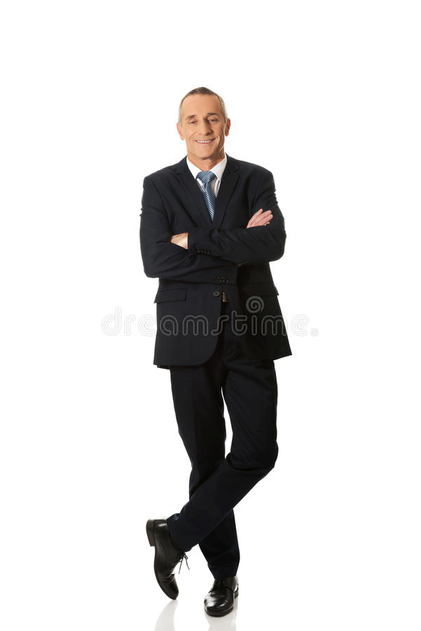 Confident businessman standing with folded arms. Mature confident businessman standing with folded arms stock image