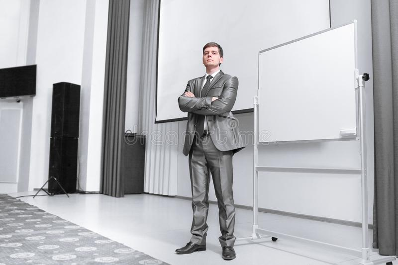 Confident businessman standing on stage in the conference hall. Business and education royalty free stock photo