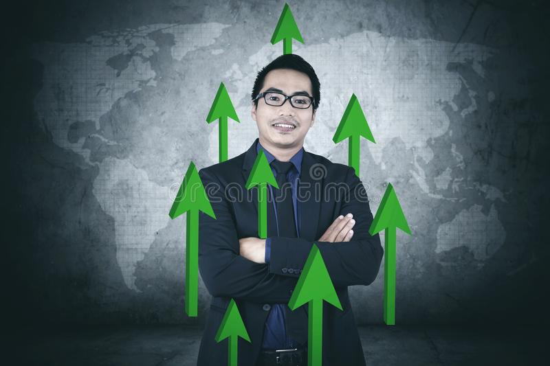 Confident businessman with upward arrows. Image of young businessman looks confident while standing with upward arrows stock photos