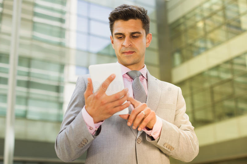 Confident businessman using cell phone royalty free stock image