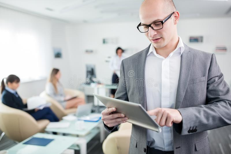 Confident Businessman Using Tablet Computer In Office stock photo
