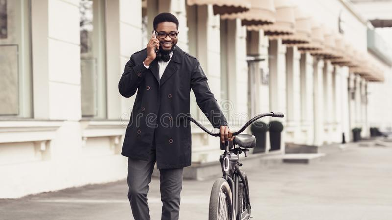Confident businessman walking with bike and talking on cellphone royalty free stock photo