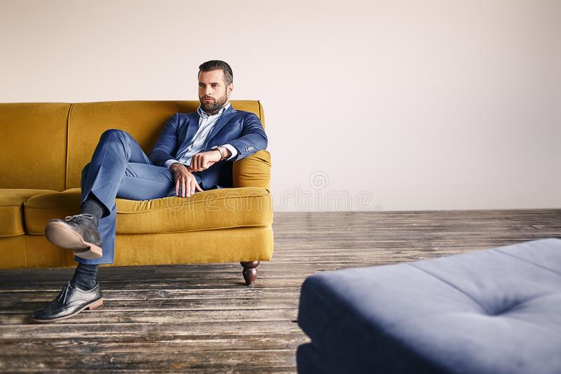 Confident businessman. Young and attractive bearded man dressed in fashionable suit is relaxing on sofa at office royalty free stock photo