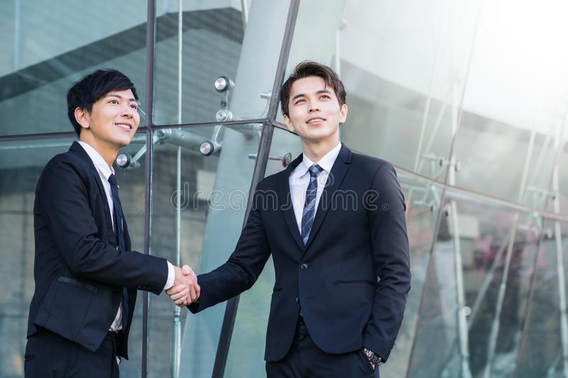 confident businessmen shaking hands and smiling royalty free stock photo