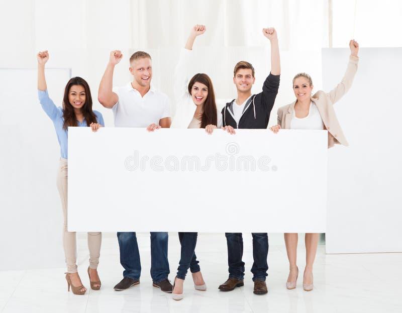 Confident businesspeople holding blank billboard stock photo
