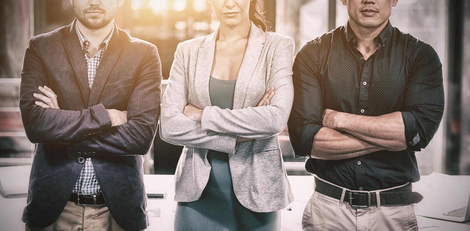 Confident businesspeople standing with arms crossed in office royalty free stock images