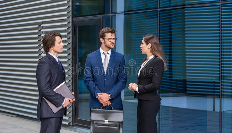 Confident businesspersons talking in front of modern office building. Businessmen and businesswoman have business. Conversation. Banking, professional job and royalty free stock photo