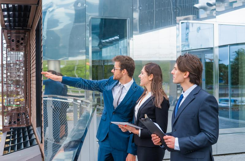 Confident businesspersons talking in front of modern office building. Businessmen and businesswoman have business. Conversation. Banking, professional job and stock photo