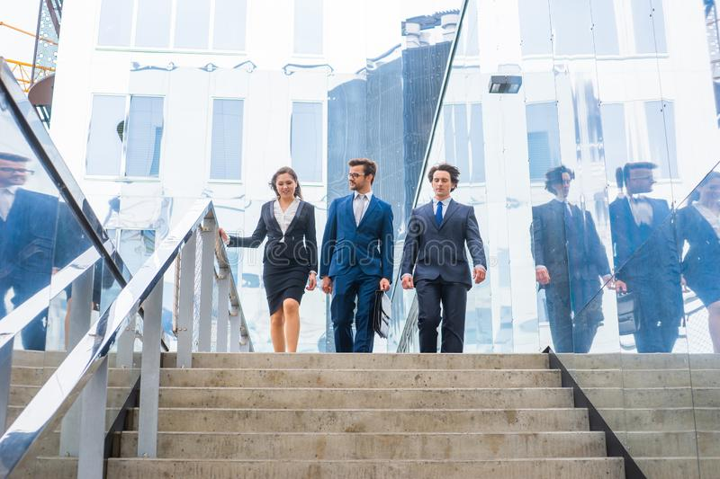 Confident businesspersons talking in front of modern office building. Businessmen and businesswoman have business. Conversation. Banking, professional job and stock images