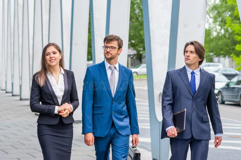 Confident businesspersons talking in front of modern office building. Businessmen and businesswoman have business. Conversation. Banking, professional job and stock image