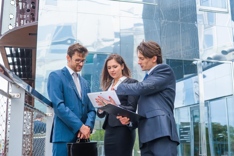 Confident businesspersons talking in front of modern office building. Businessmen and businesswoman have business. Conversation. Banking, professional job and stock photos