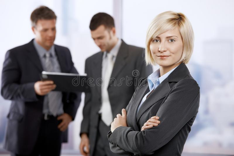 Confident businesswoman. Portrait of confident businesswoman in office lobby, smiling. Colleagues talking in the background royalty free stock image