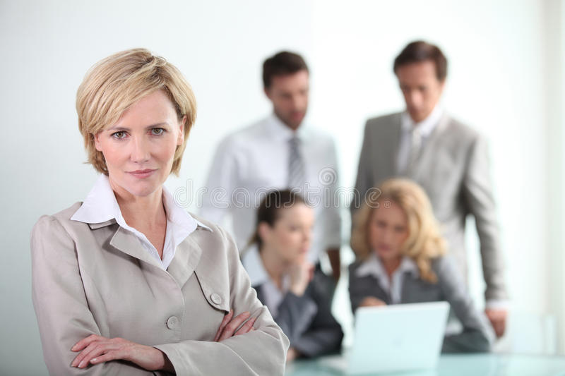 Confident businesswoman. Standing in front of her colleagues royalty free stock photo