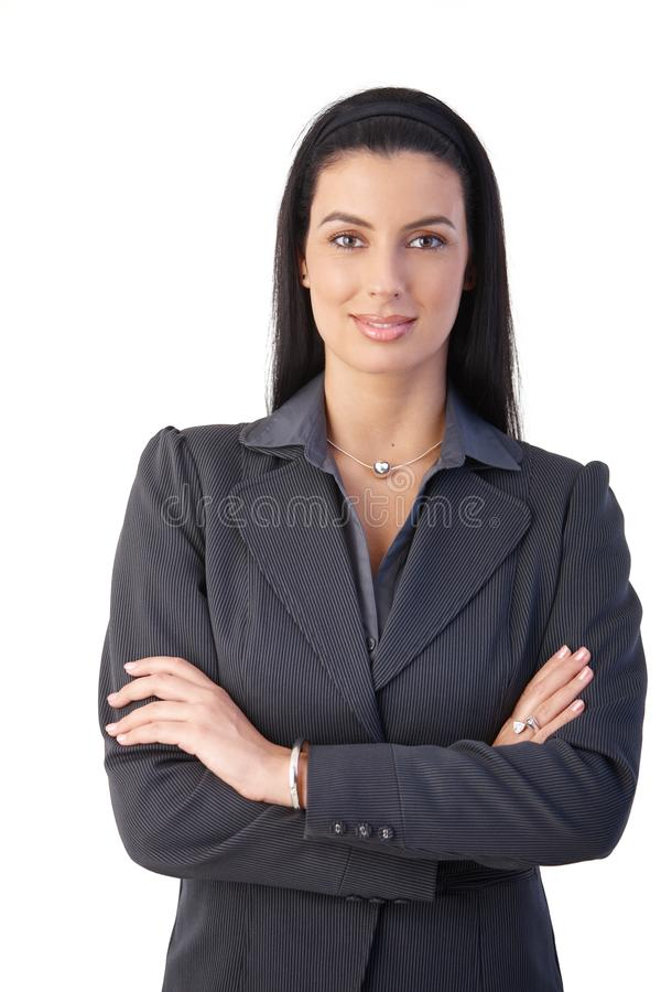 Confident businesswoman. Portrait of confident businesswoman standing with arms folded, smiling at camera royalty free stock photo