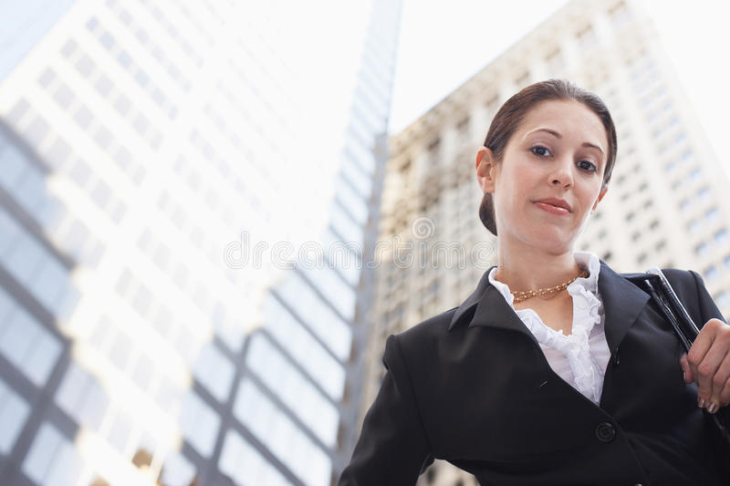 Confident Businesswoman Against Office Buildings royalty free stock image