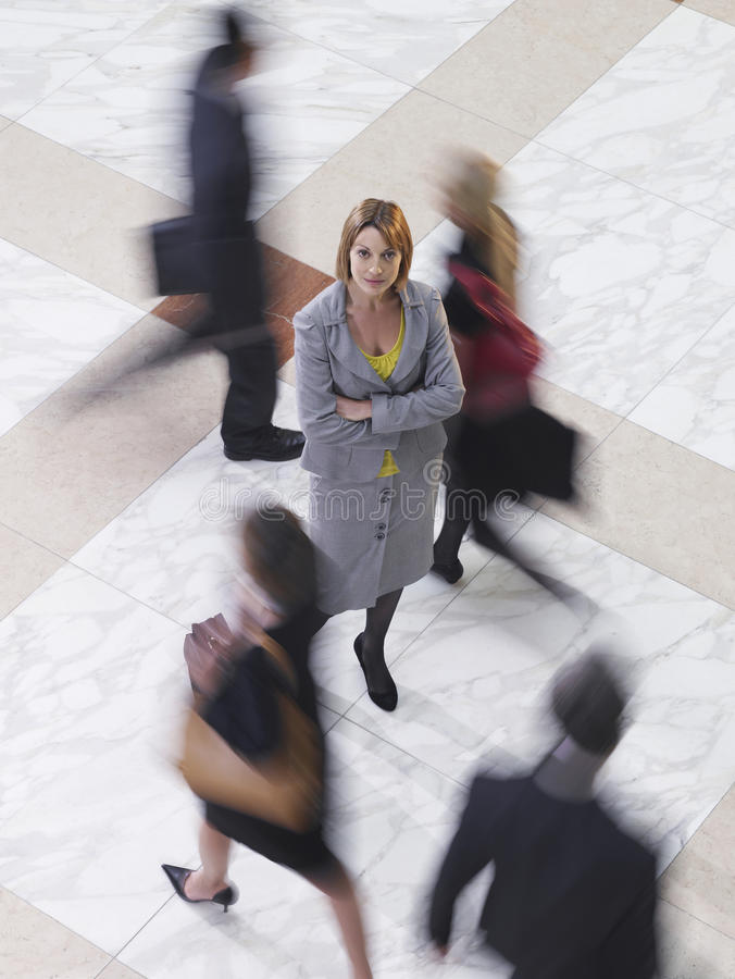 Confident Businesswoman Amid Blurred Walking People. Elevated view of a confident businesswoman amongst blurred people walking royalty free stock image