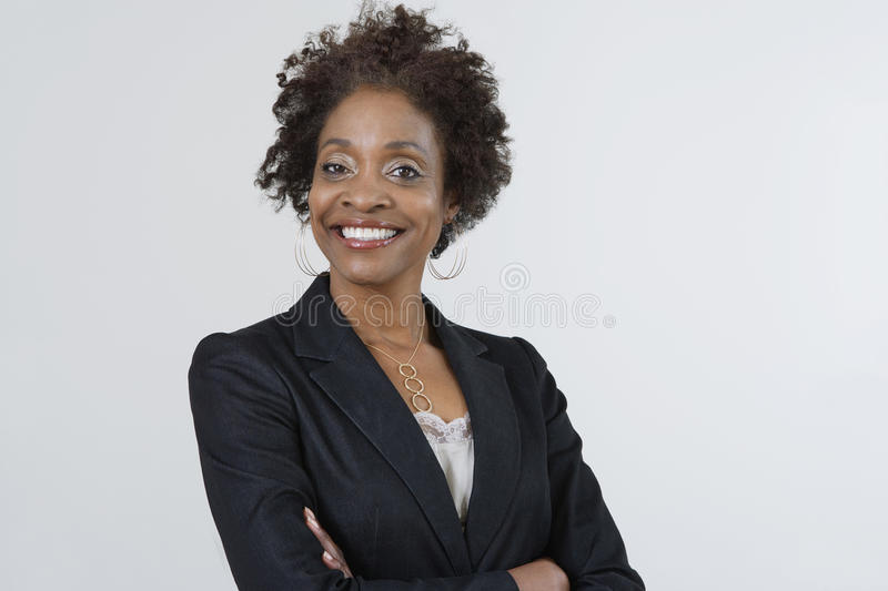 Confident Businesswoman With Arms Crossed. Portrait of a confident African American businesswoman with arms crossed isolated over white background royalty free stock image