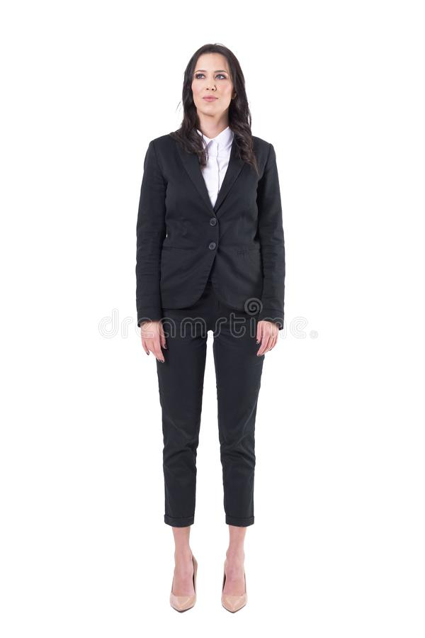Confident businesswoman in black business suit standing with arms down looking up. Full body isolated on white background stock photos
