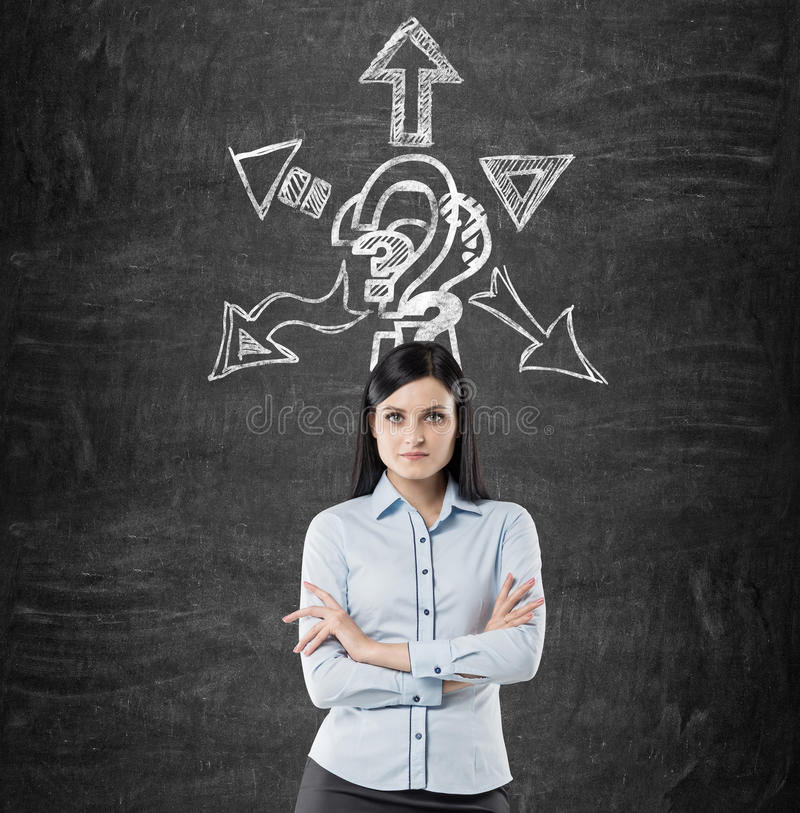 Confident businesswoman brainstorming. Portrait of a determined black haired businesswoman standing with crossed arms near a blackboard with a question mark and stock image
