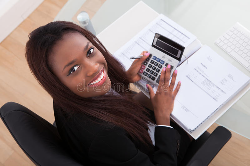 Confident businesswoman calculating tax at desk. Portrait of confident businesswoman calculating tax at desk in office royalty free stock photography