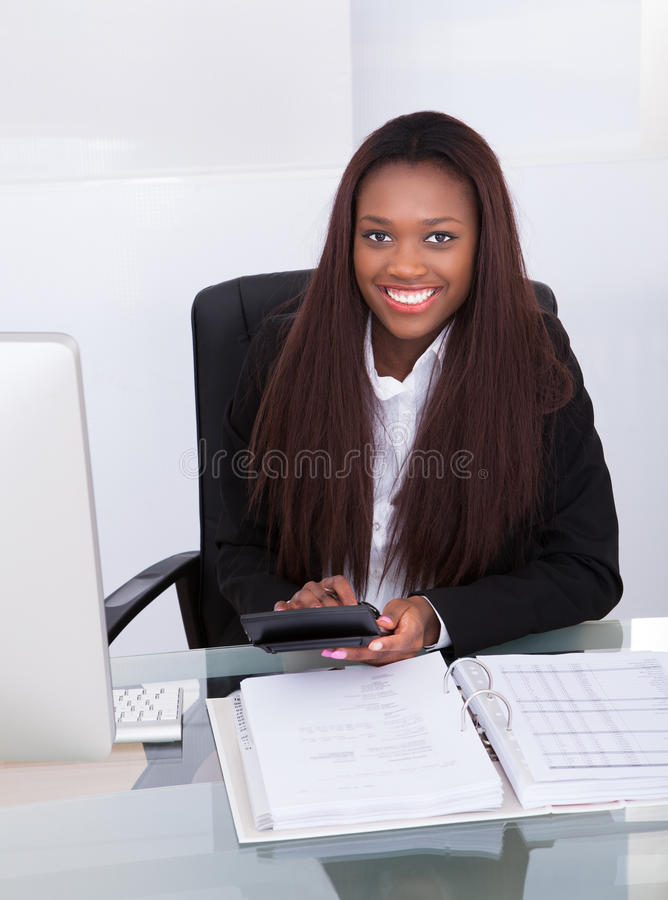 Confident businesswoman calculating tax at desk. Portrait of confident businesswoman calculating tax at desk in office royalty free stock images